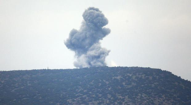 A plume of smoke from an air bombardment rises from an impact inside Syria (AP)
