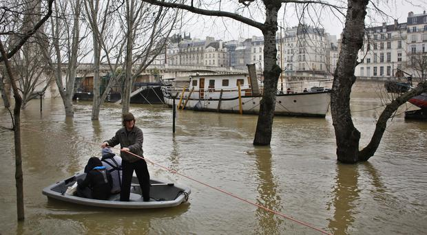 People use a dinghy boat to reach a barge on the river Seine in Paris (AP)