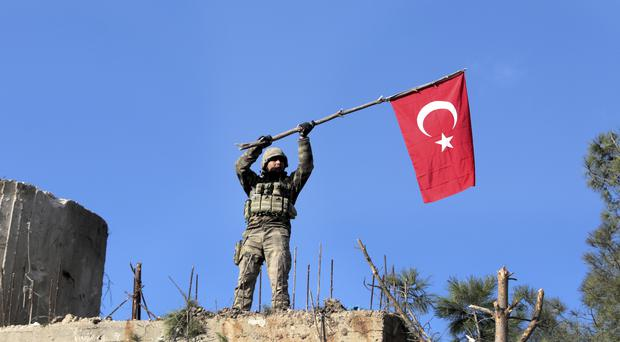 A soldier waves a Turkish flag as Turkish troops secure Bursayah hill (AP)