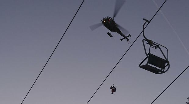 A helicopter rescues people from a broken chairlift at the Kreischberg mountain (Bundesheer/AP)