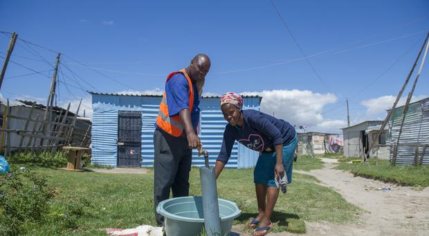 People collect water from a communal tap at an informal settlement near Cape Town (AP)