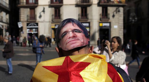 A man wears a mask of Catalonia's fugitive ex-president Carles Puigdemont (AP)