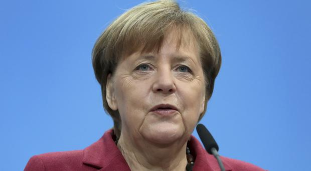 Mrs Merkel is seeking to form a new government (AP)