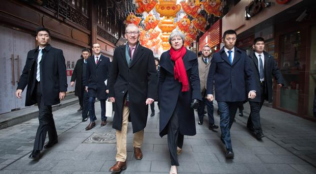 Theresa May and her husband Philip walk through a market in Shanghai (Stefan Rousseau/PA)