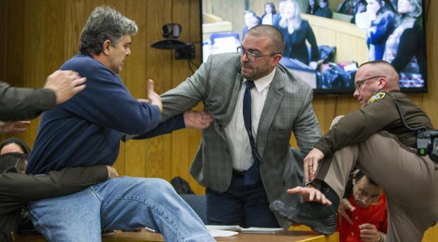 Randall Margraves, father of three victims of Larry Nassar , left, lunges at the sex offender (AP)