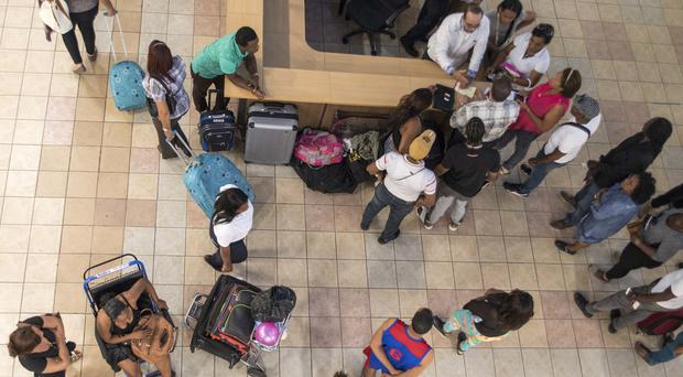 Stranded Pawa Dominicana passengers gather around the Civil Aviation Board information desk (AP)