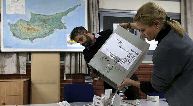 Election workers pour ballots out of ballot boxes to begin counting in Cyprus' presidential run-off at a polling station in Ayioi Omologites primary school in Nicosia (Petros Karadjias/AP)