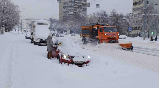A woman clears snow from her car in Moscow (Igor Mikhalev/AP)