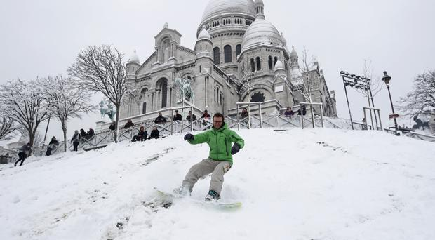 Geoffrey, 32, rides his snowboard down the Montmartre hill (AP)