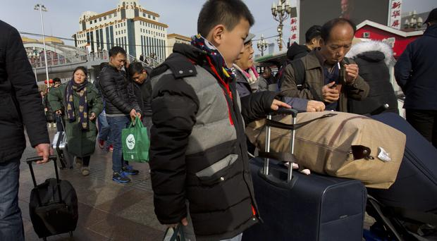 Travellers outside Beijing Railway Station (Mark Schiefelbein/AP)