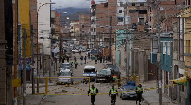 Police stand guard at the site of the second explosion in Oruro, Bolivia (Juan Karita/AP)