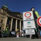 Environment activists stand in front of the Federal Administrative Court in Leipzig (Sebastian Willnow/dpa via AP)