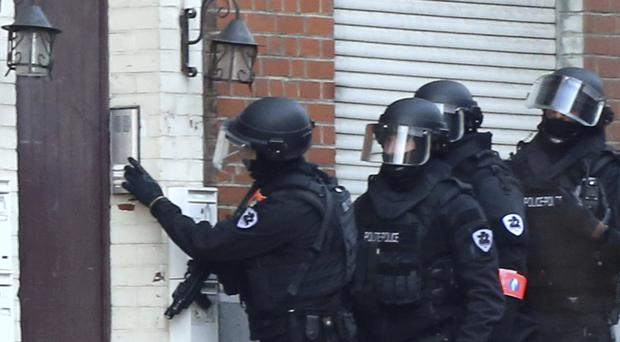 Police investigate a doorway during a police operation in Brussels (AP Photo/Francois Walschaerts)