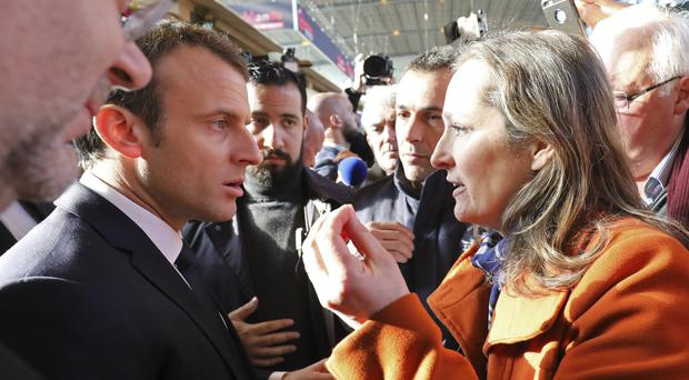 A woman protests at French President Emmanuel Macron at the 55th International Agriculture Fair at the Porte de Versailles exhibition centre in Paris (Ludovic Marin/AP)