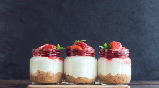 Sweet homemade cheesecake with strawberries in the jar on wooden background,selective focus