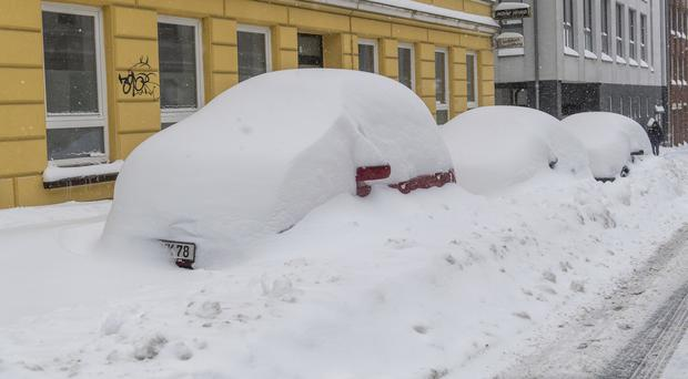 Snow-covered cars are parked in a street in Flensburg, German (AP)