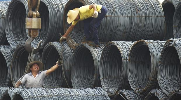 Labourers work in the steel market in Yichang in central China's Hubei province (AP)