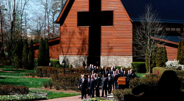 A casket carrying the body of Rev Billy Graham is carried to his funeral service at the Billy Graham Library in Charlotte, North Carolina, yesterday