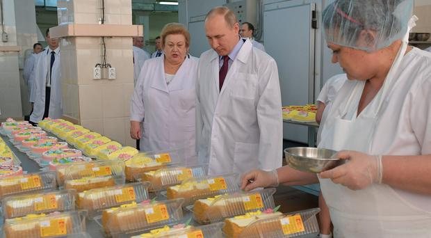 Russian president Vladimir Putin looks at bread and confectionery during his visit to the Samara bakery (Alexei Druzhinin, Sputnik, Kremlin Pool Photo/AP)