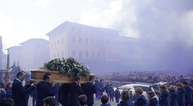 The coffin leaves the church in a purple smoke screen at the end of the funeral ceremony of Italian player Davide Astori in Florence, Italy (Alessandra Tarantini/AP)