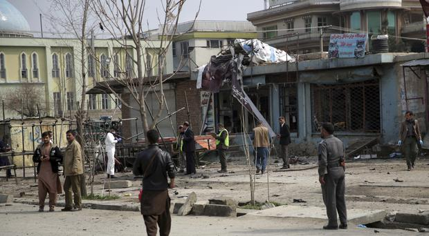Security personnel inspec the site of the suicide attack in Kabul (Massoud Hossaini/AP)