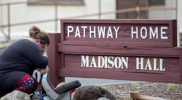 A woman, who declined to give her name, cries after placing flowers at a sign at the Veterans Home of California, the morning after a hostage situation in Yountville, California (Josh Edelson/AP)
