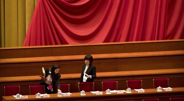 Staff members arrange paperwork on the rostrum before a plenary session of China's National People's Congress at the Great Hall of the People in Beijing (Mark Schiefelbein/AP)