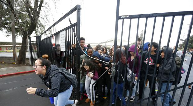 Students from Mount Diablo High School break through a gate (Aric Crabb/East Bay Times/AP)