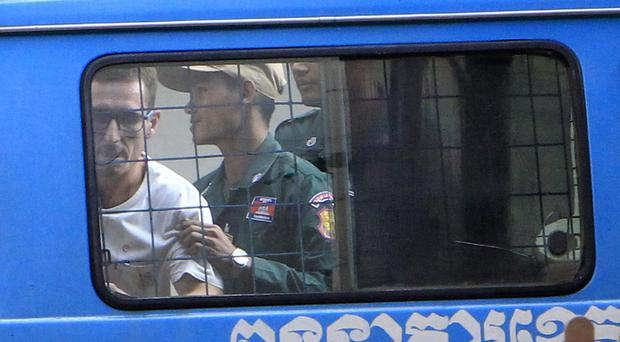 Daniel Jones, left, is escorted by a prison guard to a waiting van outside the Siem Reap court (AP Photo/Heng Sinith)