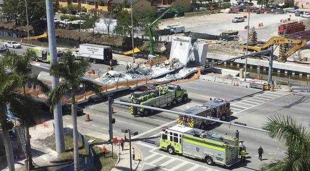 Emergency personnel responds to a collapsed pedestrian bridge connecting Florida International University Florida International (Roberto Koltun/AP)