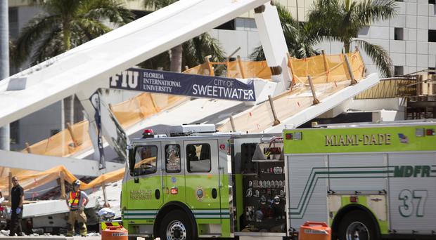 Emergency personnel respond to a collapsed pedestrian bridge (Daniel A. Varela/AP)