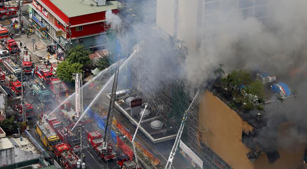 Firemen battle a fire at the Manila Pavillion Hotel (Bullit Marquez/AP)