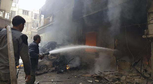 Civil Defence workers putting out a fire following air strikes and shelling in eastern Ghouta (Syrian Civil Defence White Helmets via AP)