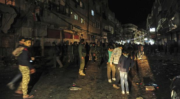Syrians gather at the site of a deadly mortar assault on a market in the Kashkol neighbourhood of Damascus (SANA via AP)