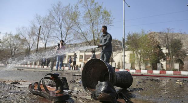 Afghan firefighters clean up the site of a deadly suicide bombing in Kabul (Rahmat Gul/AP)