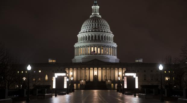 The Capitol is seen before dawn Wednesday after a night of negotiating on the government spending bill (AP Photo/J. Scott Applewhite)