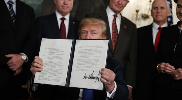 President Donald Trump displays signs a presidential memorandum imposing tariffs and investment restrictions on China in the Diplomatic Reception Room of the White House (Evan Vucci/AP)