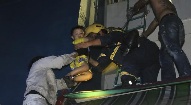 A boy is rescued from the apartment blaze in Ho Chi Minh City (VnExpress via AP)