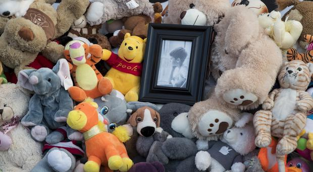 A portrait of a boy is surrounded by toys as people bring them to commemorate the victims of Sunday's fire in a shopping mall in the Siberian city of Kemerovo (Pavel Golovkin/AP)