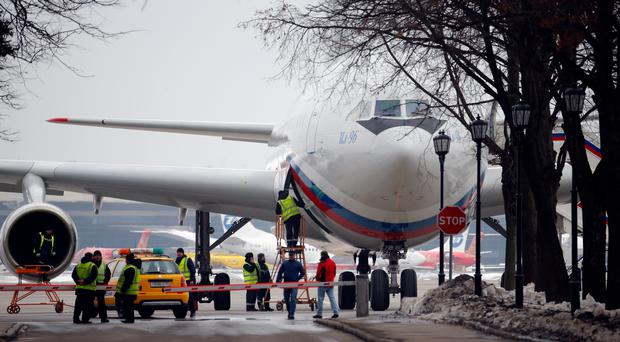 A plane carrying Russian diplomats and their family members ordered to leave the US lands at Vnukovo 2 government airport outside Moscow (Alexander Zemlianichenko/AP)