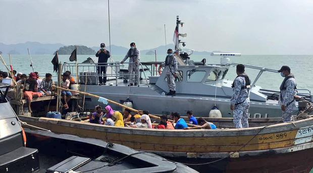 Malaysian navy officers detaining a boat carrying Rohingya migrants in Langkawi, Malaysia (Royal Malaysian Navy via AP)