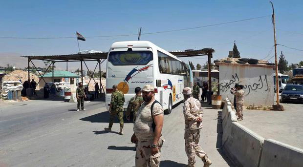 Syrian government forces oversee the evacuation by bus of Army of Islam fighters from the besieged town of Douma (SANA via AP)