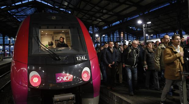 Commuters arrive at a train station in Paris (Christophe Ena/AP)