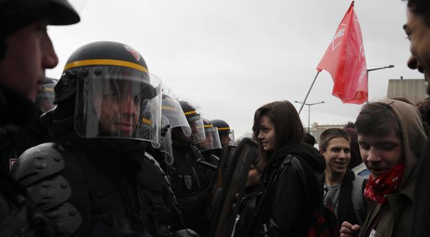 Students face a riot police officer as they demonstrate outside the Rouen hospital, Normandy. (Christophe Ena/PA)
