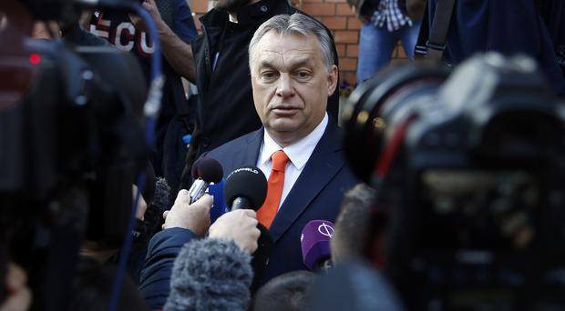 Hungary's prime minister Viktor Orban addresses the media outside a polling station in Budapest (AP)