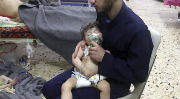 A medical worker giving a toddler oxygen near Douma (Syrian Civil Defence White Helmets/AP)
