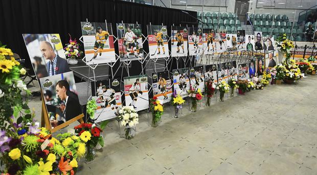 Photos of people involved in a fatal bus crash are seen prior to a vigil at the Elgar Petersen Arena (Jonathan Hayward/The Canadian Press via AP)