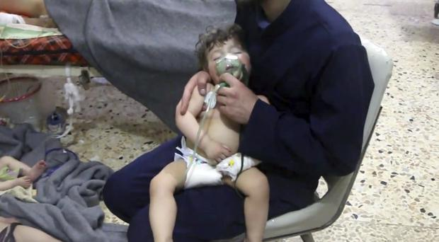 A medical worker gives toddlers oxygen following an alleged poison gas attack in Douma (Syrian Civil Defense White Helmets/AP)