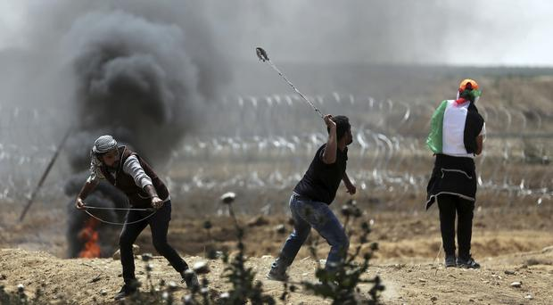 Palestinian protesters hurl stones at Israeli troops (AP Photo/ Khalil Hamra)