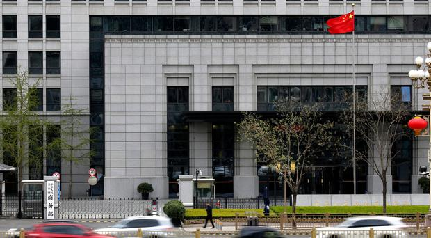 Motorists drive past China's Ministry of Commerce in Beijing (Andy Wong/PA)